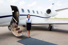 Hôtesse de l'air se tenant prêt le jet privé Photographie stock
