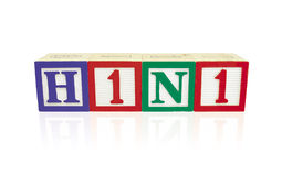 H1N1 Alphabet Blocks with reflection. Alphabet blocks arranged horizontally on a reflective white surface to spell 'H1N1 Royalty Free Stock Photography