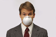 H1N1 scared businessman. Businessman with mask shows fear of H1N1 flu virus Stock Images