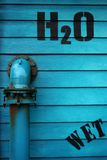 H2O Water Hydrant. Water hydrant with a blue stained wood background Stock Image