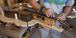H31 Filing the bridges. Luthier doing finishing work on flamenco guitar Stock Image