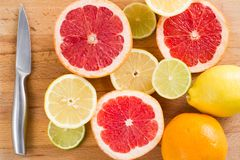 Ha affettato i limoni freschi dell'agrume, le calce, i pompelmi, arance su un tagliere di legno con un coltello del metallo, vist fotografie stock libere da diritti