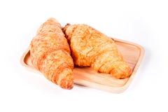 Ha cotto di recente il croissant sui croissant freschi e saporiti di legno del piatto, isolati su un fondo bianco immagine stock