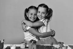 Ha en trevlig dag Konstnärer med hästsvansleende Flickor med lyckliga framsidor vid skrivbordet Fotografering för Bildbyråer