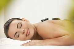 ha för stenbehandling för varm massage den avslappnande kvinnan Royaltyfri Bild