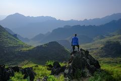 Ha Giang / Vietnam - 01/11/2017: Backpacker standing on outcrop overlooking karst mountain scenery in the North Vietnamese region royalty free stock photos
