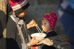 Ha Giang, Vietnam - Feb 14, 2016: Hmong mother feed her son with instant noodle in Dong Van market, Asian.  Royalty Free Stock Images