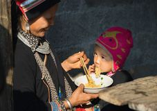 Ha Giang, Vietnam - Feb 14, 2016: Hmong mother feed her son with instant noodle in Dong Van market, Asian.  Stock Image