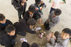 Ha Giang, Vietnam - Feb 7, 2014: Unidentified group of Hmong children playing cards in an old market.  Stock Photo