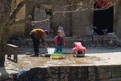 Ha Giang Vietnam - Februari 14, 2016: Hmong farmorhjälp hennes barn som framme tvättar deras hår av huset i distric Dong Van Arkivbild