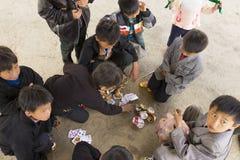 Ha Giang Vietnam - Februari 7, 2014: Oidentifierad grupp av Hmong barn som spelar kort i en gammal marknad Arkivfoto