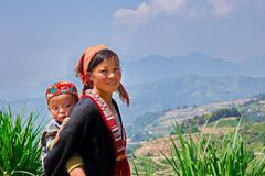 Ethnic mom and her child on the mountain near ripen rice terraces. stock photo