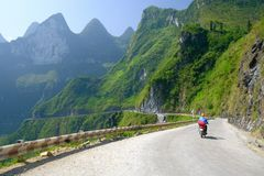 Ha Giang / Vietnam - 01/11/2017: Motorbiking backpackers on winding roads through valleys and karst mountain scenery in the North royalty free stock photo