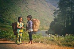 Ha Giang Vietnam - 02 November, 2012: Två ungdomargår att arbeta tillsammans på berget Royaltyfria Bilder