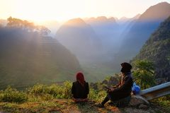 Ha Giang / Vietnam - 01/11/2017: Two local Vietnamese women in traditional clothes looking at the sunrise and mountain scenery in royalty free stock photography