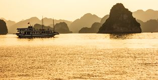 Ha Long bay islands, tourist boats and seascape in the evening with golden light reflection on water, Ha Long, Vietnam.  stock photos