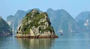 Ha Long Bay Limestone karsts with fishing boat in middle distance. Limestone karsts with fishing boat in middle distance  - popular travel destination  - scenic Stock Image
