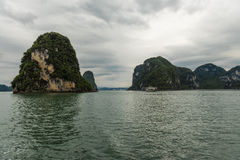 On Ha Long Bay. Sailing on Ha Long with Large Rock Formations and Cloudy Skies Royalty Free Stock Photo