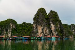 Floating village in Ha Long Bay, Vietnam, with rain in the foreground and mist in the distance royalty free stock photography