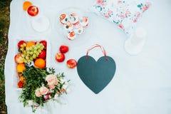 Ha picknick på gläntan för vänner med frukt och kakor, svart svart tavla i form av en hjärta, en kärlekshistoria Arkivfoto