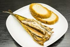 Ha preparato mangiare lo sgombro affumicato su un piatto con le fette di pane Immagine Stock