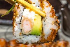 Ha preso del uramaki con il gamberetto della tempura Immagini Stock Libere da Diritti