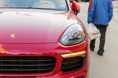 Ha vestito male le passeggiate dell'uomo senior giù la via dopo un'automobile rossa di Porsche Concetto di lusso e di povertà Con fotografia stock libera da diritti