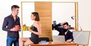 Ha vila för bra arbete Nätt kvinna och stilig man som har att vila i regeringsställning medan kollega som arbetar i bakgrund arkivfoton