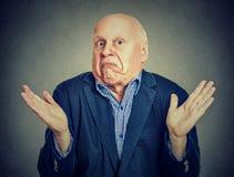 Haalt de oudste verwarde mens zijn schouders op stock fotografie