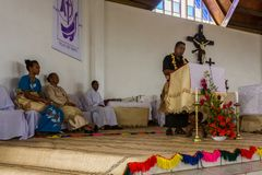 Traditionally dressed Polynesian priest and congregation at Catholic Mass in church. Haapai Group in Tonga, Polynesia. stock photos