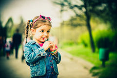 Haappy little girl with candy outdoor in the park Stock Photography