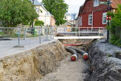 Haapsalu, Estonia, 12.07.2020. Underground heating system pipes replacement on the city street among the houses.