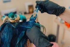 Haar die in heldere kleuren verven Borstel en blauwe verf stock afbeeldingen