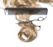 Haar mit Haarausschnittscheren und -kamm Stockbild