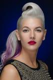Haar und Make-upthema: schöne junge blonde Frau mit dem kreativen Haar, das mit den roten Lippen auf einem dunkelblauen Hintergru Stockbilder