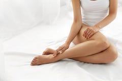 Haarabbau Schließen Sie herauf die Frauen-Hände, die lange Beine, weiche Haut berühren Stockfotografie