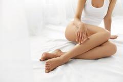 Haarabbau Schließen Sie herauf die Frauen-Hände, die lange Beine, weiche Haut berühren Lizenzfreies Stockbild