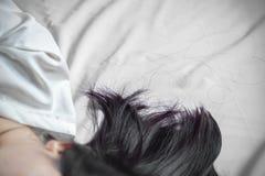 Haarausfall von der Asiatin, die auf Bett schläft Stockfotos