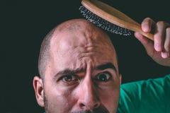 Haarausfallkonzept Kahler Mann, der Haarbürste auf nicht vorhandenem Haar verwendet lizenzfreie stockfotos