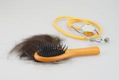 Haarbürste mit dem braunem verlorenem Haar und Stethoskop Stockfoto