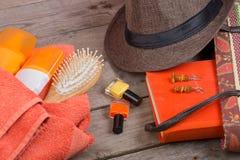 Haarbürste, orange Tuch, Hut, Sonnencreme, Lotion, Strandtasche, Nagellack, ein Buch auf einem braunen hölzernen Hintergrund stockfotos