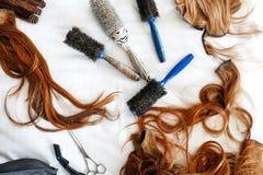Haarbürsten und falsches Haar mit Scheren stockfotos