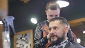 Haarblick magisch machen Junger bärtiger Mann, der Haarschnitt mit Latterasiermesser durch Friseur beim herein sitzen erhält stock footage