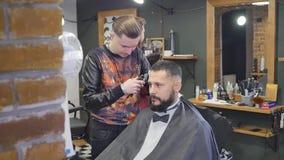 Haarblick magisch machen Junger bärtiger Mann, der Haarschnitt mit Latterasiermesser durch Friseur beim herein sitzen erhält stock video