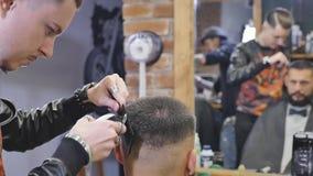 Haarblick magisch machen Junger bärtiger Mann, der Haarschnitt mit Latterasiermesser durch Friseur beim herein sitzen erhält stock video footage