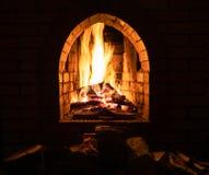 Haard met het branden van brandhout bij nacht stock fotografie