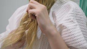 Haargezondheid, het concept van het haarverlies Vrouw die haar blond beschadigd droog haar in de badkamers kammen stock videobeelden