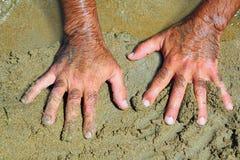 Haarige Mannhände auf Strandsand am sonnigen Sommer Lizenzfreies Stockfoto