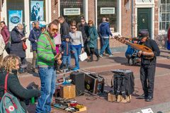 Haarlem, Netherlands – April 14, 2019:  a street musician with a guitar and a singer on a city street royalty free stock photography