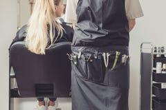 Haaropmaker met het kappenhulpmiddelen in salon stock afbeelding